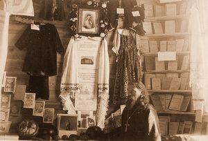 Священнослужитель у стенда со школьными принадлежностями и учебниками и экспонатами выставки.