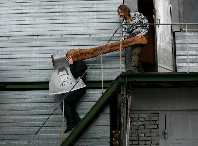 Russian artist Vasily Slonov and an assistant carry a giant axe decorated with a portrait of Russian businessman and politician Mikhail Prokhorov from his workshop as he prepares for an exhibition of his new art project in Russia's Siberian city of Krasno