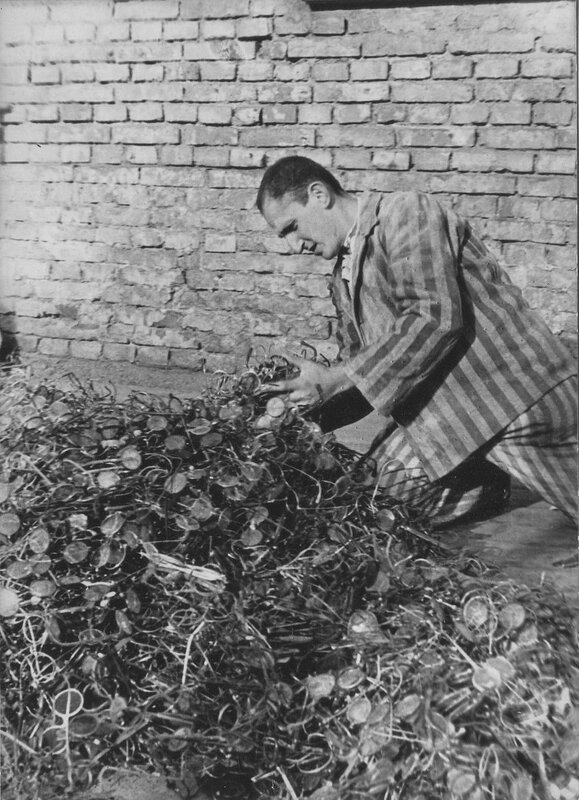 Бывший узник концлагеря Освенцим подбирает себе очки среди большой кучи очков, отобранных у заключенных