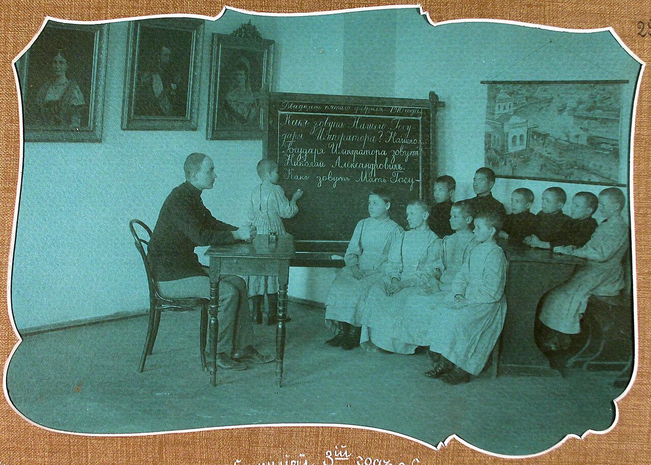 Учитель обучает детей 3-го года обучения правильному написанию имен членов императорской фамилии