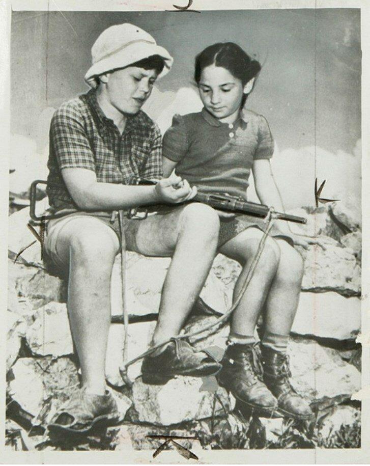 Двенадцатилетний мальчик учит девочку пользоваться автоматом в мае 1948