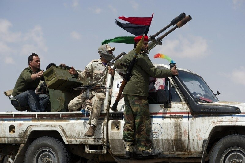 Libyan rebels ride a pick-up truck durin