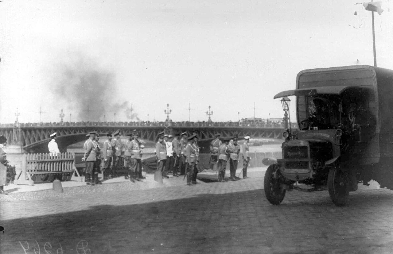 04.  Император Николай II со свитой наблюдает за приезжающими грузовиками на Дворцовой набережной у Троицкого моста