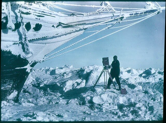 Frank Hurley photographing under the bows of the 'Endurance', 1915
