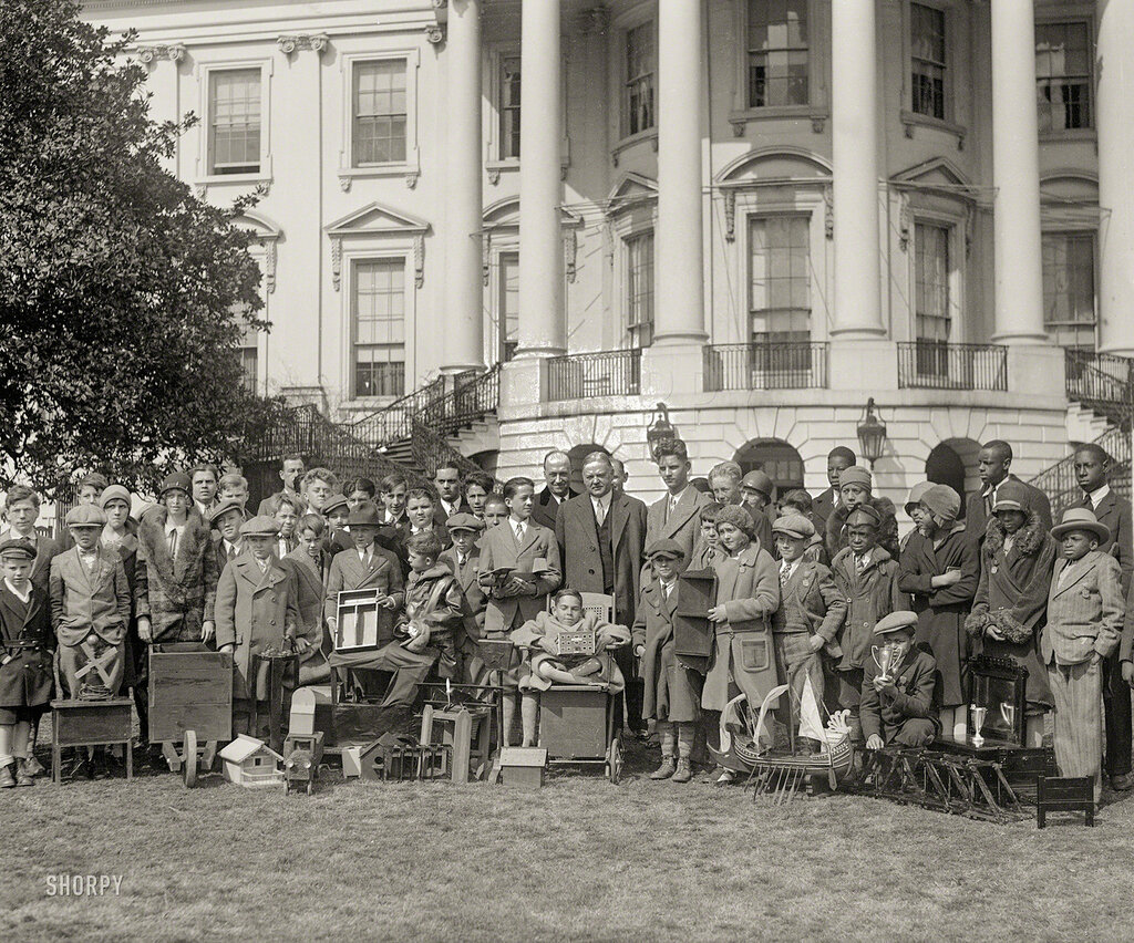 Circa 1930. President Hoover with boys and girls at White House. The Department of Commerce sponsored a nationwide woodworking competition for children