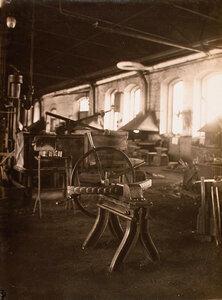 Вид тисков с зажатой в них деталью (на первом плане) в одном из цехов мастерской.
