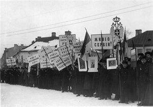 Группа манифестантов с плакатами и правительственными флагами.
