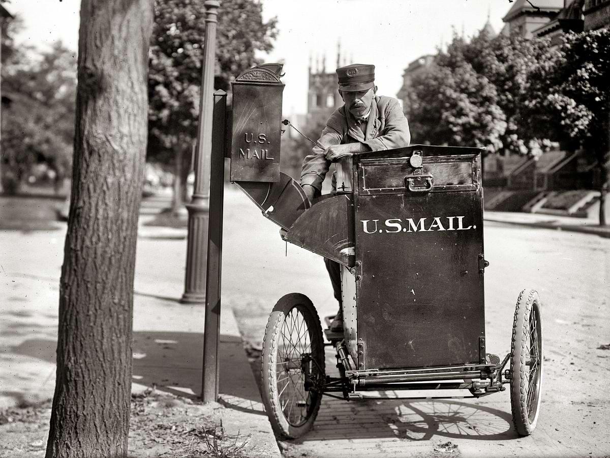 Почтальон на трехколесном мотоцикле выбирает корреспонденцию из уличного почтового ящика (Вашингтон, 1912 год)