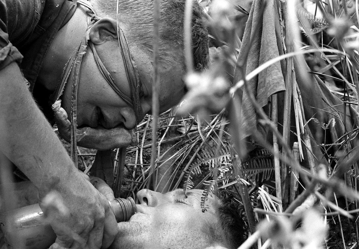 Легкораненый американский морпех поит водой своего тяжело раненого товарища во время спецоперации вдоль демилитаризованной зоны между Севером и Югом Вьетнама