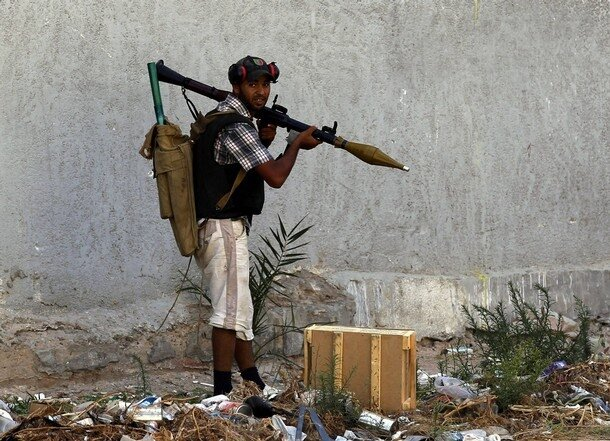 A rebel fighter holds an RPG during a fire fight with soldiers loyal to Libyan leader Muammar Gaddafi in Tripoli