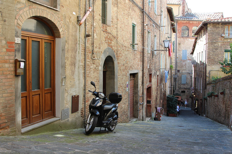 Закоулок с мотоциклом в городе Сиена