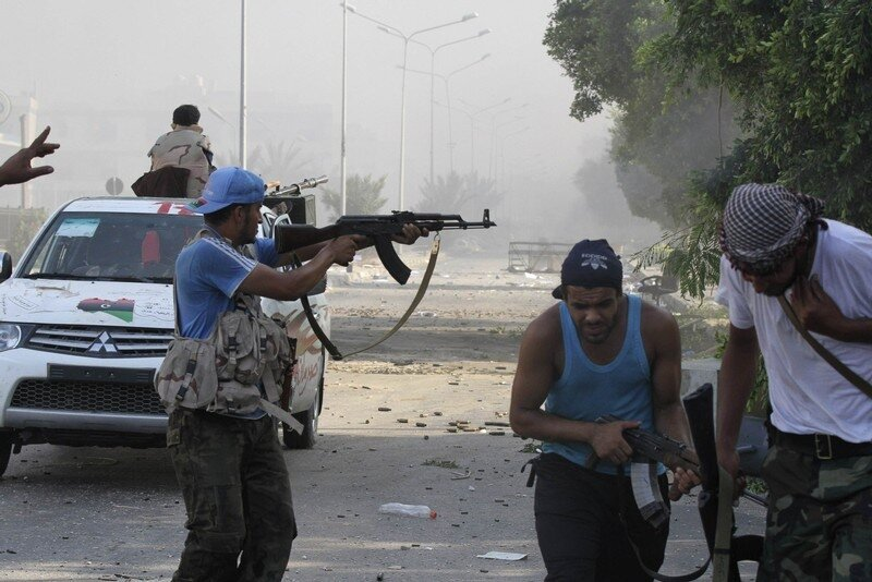 Libyan rebel fighters fire their weapons during a fight for the final push to flush out Muammar Gaddafi's forces in Abu Salim district in Tripoli
