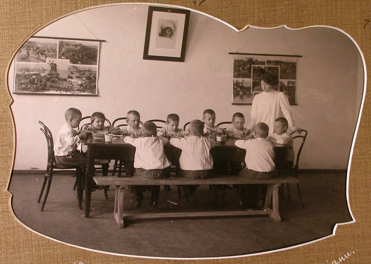 Воспитательница детского сада проводит занятие с детьми по системе Фребеля
