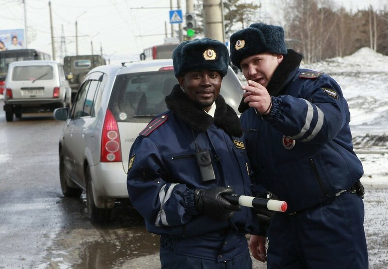 Samuel Brako from Ghana, a student of Krasnoyarsk University dressed as a road policeman, listens to an officer's instructions on a street in Russia's Siberian city of Krasnoyarsk