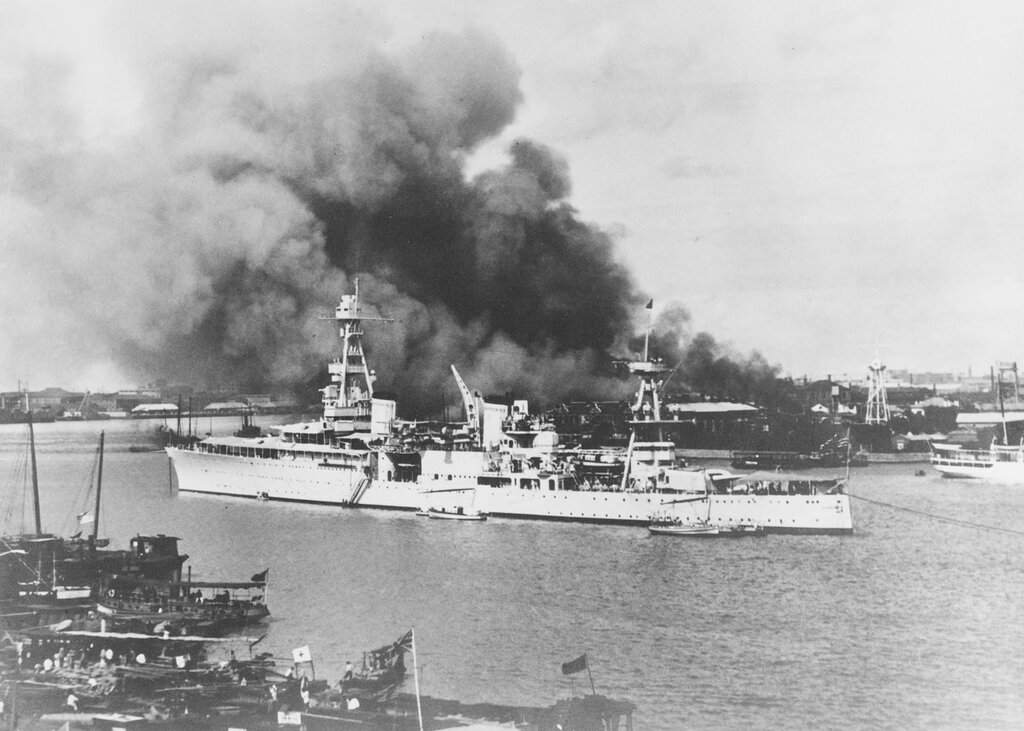 USS Augusta (CA-31) Anchored off Pootung Point, Shanghai, China, during Sino-Japanese hostilities, circa August 1937. Fires from combat action are burning ashore, beyond the ship.