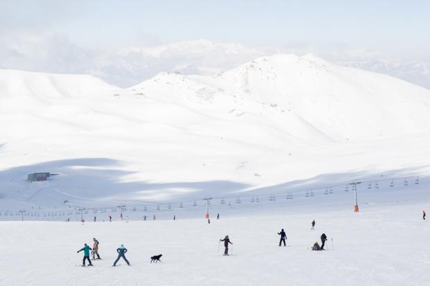 Разбросанные по склону лыжники и собака на горнолыжном курорте Точал в горах Альборз 14 декабря 2014