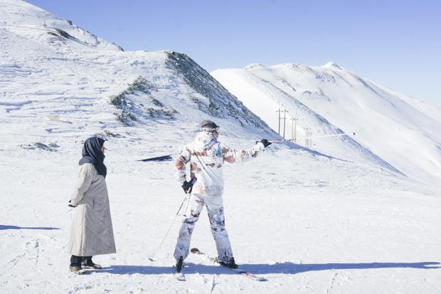 Мужчина показывает матери склоны, на которых он будет кататься, в Точале, горы Альборз, 6 января 201