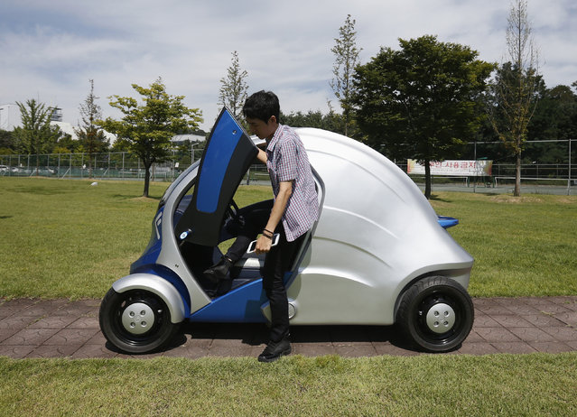 """A researcher gets out of """"Armadillo-T"""", a foldable electric vehicle, at the Korea Advanced Institute"""