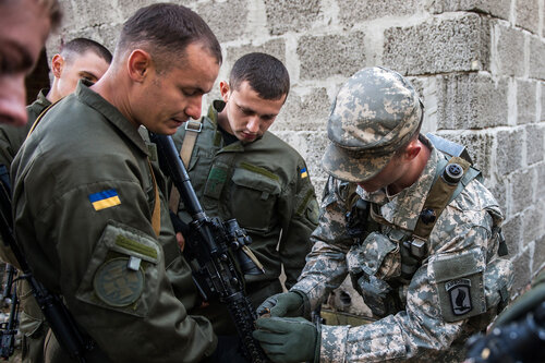 YAVORIV, Ukraine -- Sgt. Richard Lacombe, a Soldier from U.S. Army Europe's Charlie Co., 173rd Airborne Brigade shows Ukrainian National Guard Soldiers the proper procedures for operating an M4 rifle during situational training exercise lanes at Rapid Tri