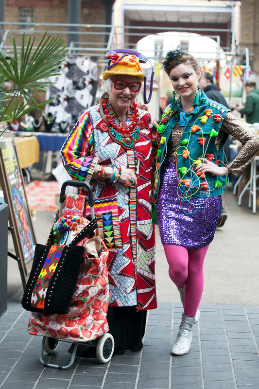 Brightly dressed women in typical East London style on Brick Lane. Street fashion.