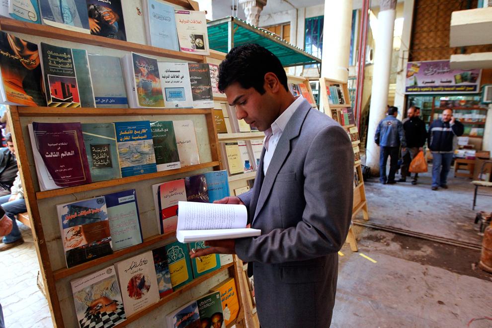 14. Мужчина читает книгу на улице Мутанаби в Багдаде. (Thaier al-Sudani/Reuters)