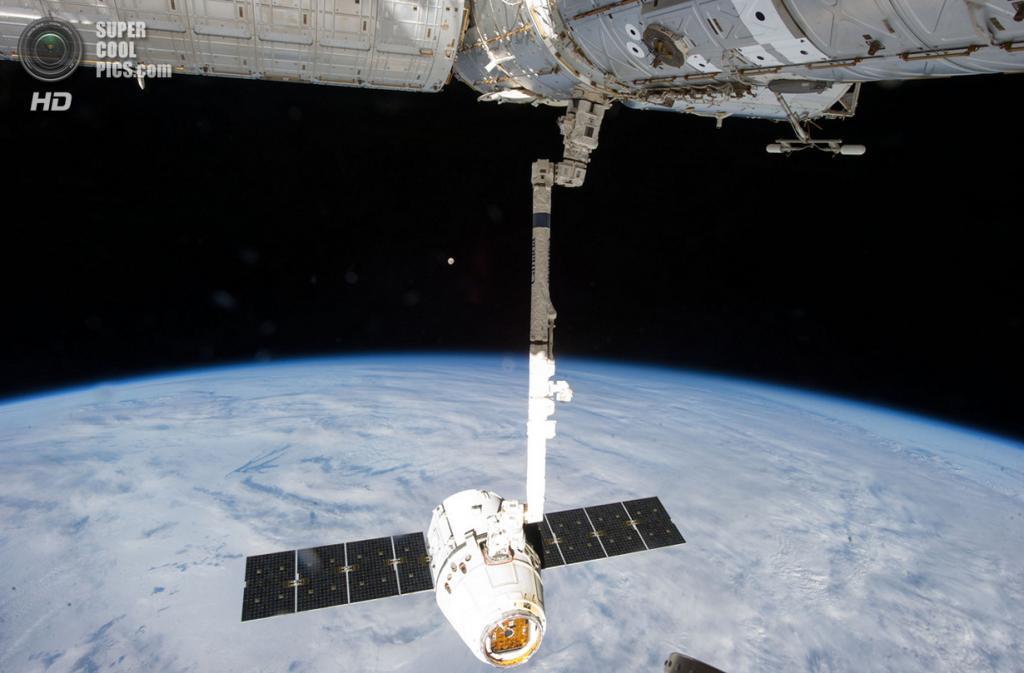 26 марта. Роботическая рука МКС CanadArm2 держит космический корабль SpaceX «Дракон» во время ег