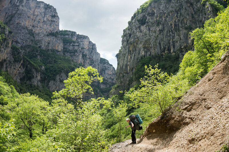 пеший турист с рюкзаком на тропе по ущелью Викос (path in Vikos gorge)