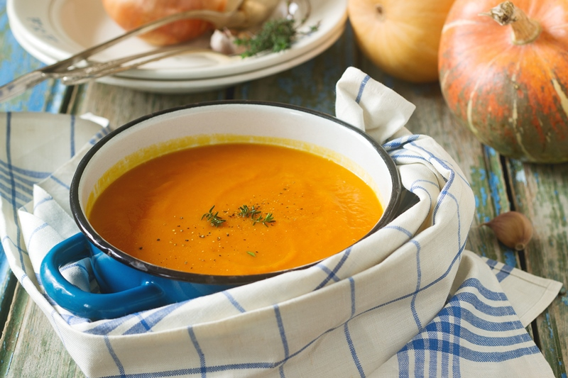 Pumpkin cream soup in a blue saucepan on a wooden background. Rustic style, selective focus.