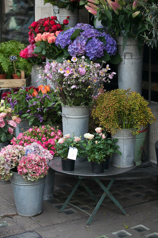 the Various flowers at the entrance to the store for sale for various occasions: weddings, birthdays, mother's day, Valentine's Day