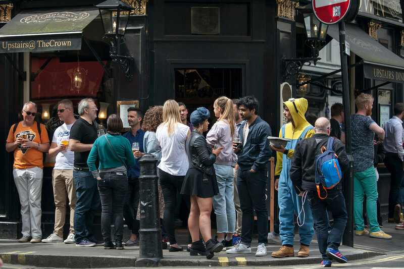 LONDON, ENGLAND - August 11 2017 Men and women drink beer and smoke outside the Crown pub near Leicester square on a sunny day