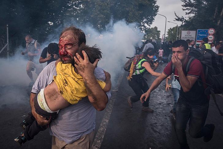 Мужчина пытается защитить своего ребенка от ударов полиции и слезоточивого газа на границе в сербско