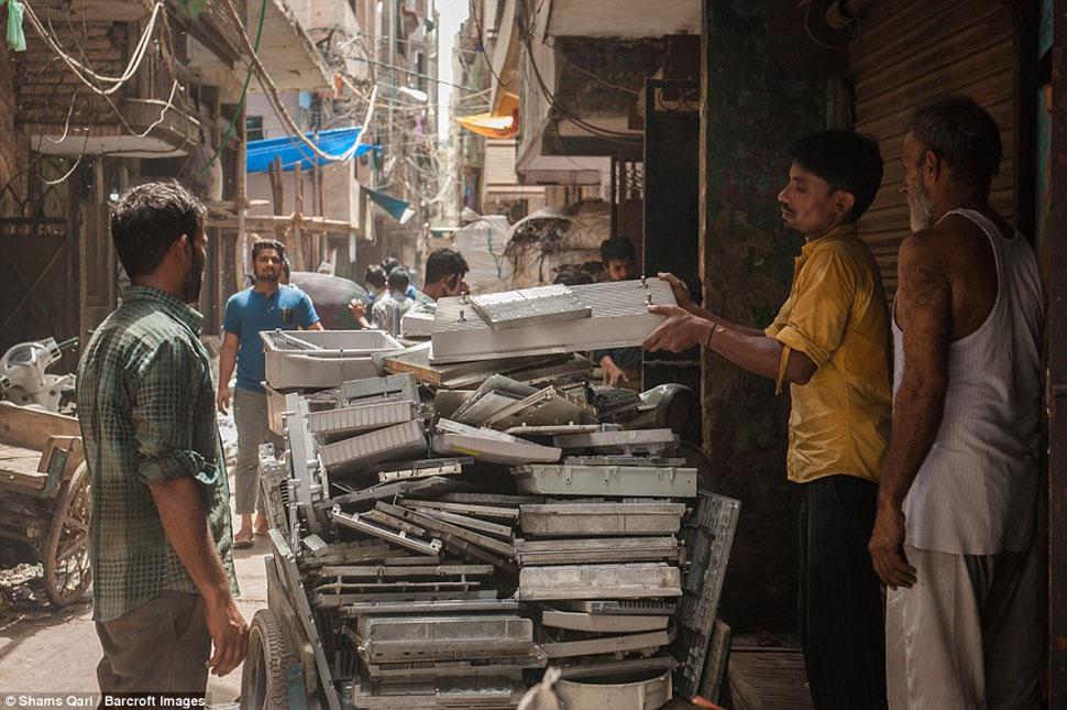Рабочие разгружают тележку с деталями от старой электроники.