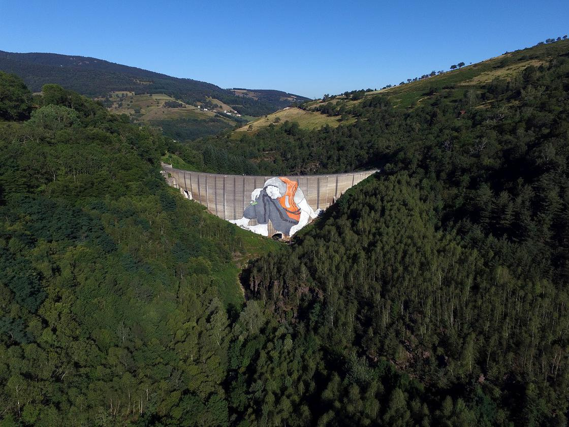 Ella and Pitr paint a gigantic refugee on the Piney's dam