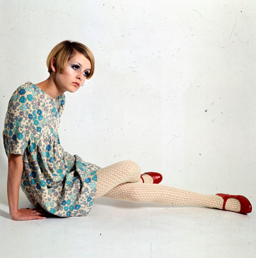 Sixties Fashion - English fashion model Twiggy posed wearing a short summer dress with white knitted tights and red shoes circa 1966. (Photo by Popperfoto/Getty Images)