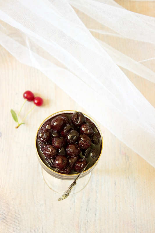 Glass with homemade Cherry Jam on wooden background