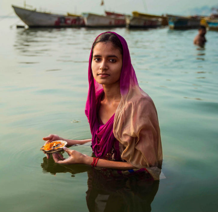 Молодая паломница и индуистка делает подношение в реке Ганг в Варанаси. Город считается духовной сто