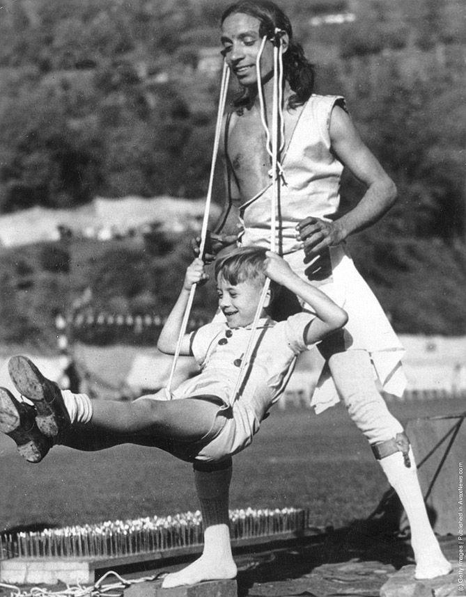 12. 1960 год.   Индийский «мастер» раскачивает прикрепленный к его волосам слинг с ребенком, чт