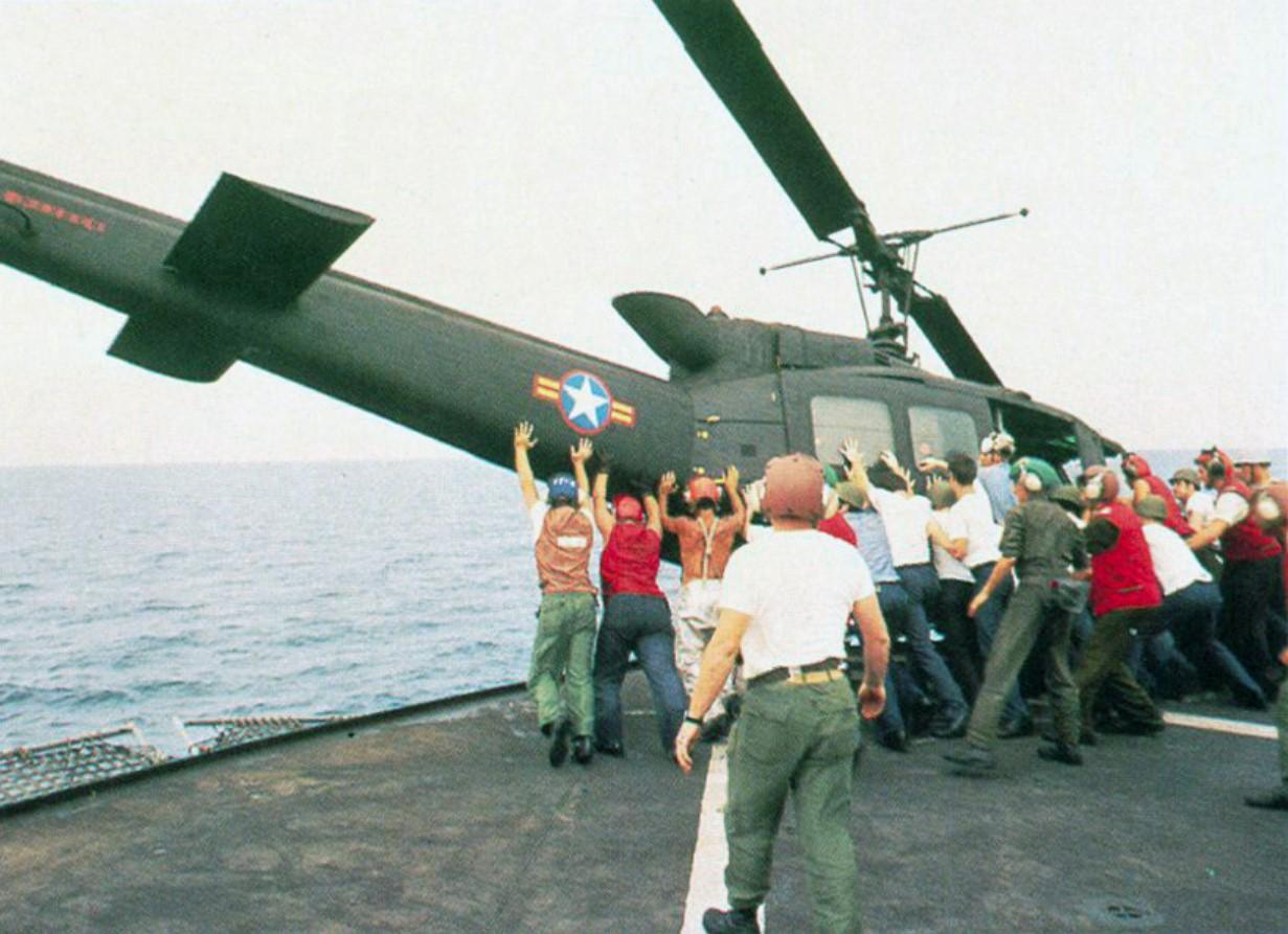 Вертолет UH-1H выталкивается за борт, чтобы освободить место для посадки Cessna O-1. Операция «Порывистый ветер»  началась 29 апреля 1975 года. Морские пехотинцы сажали американских и вьетнамских гражданских лиц, опасавшихся за свою жизнь, на вертолеты, к