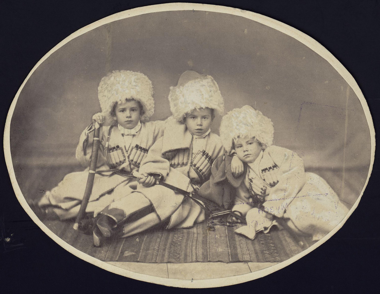 Трое детей в черкесских костюмах, на коврике. Крайний справа – Николай Сумароков-Эльстон. 1880-е