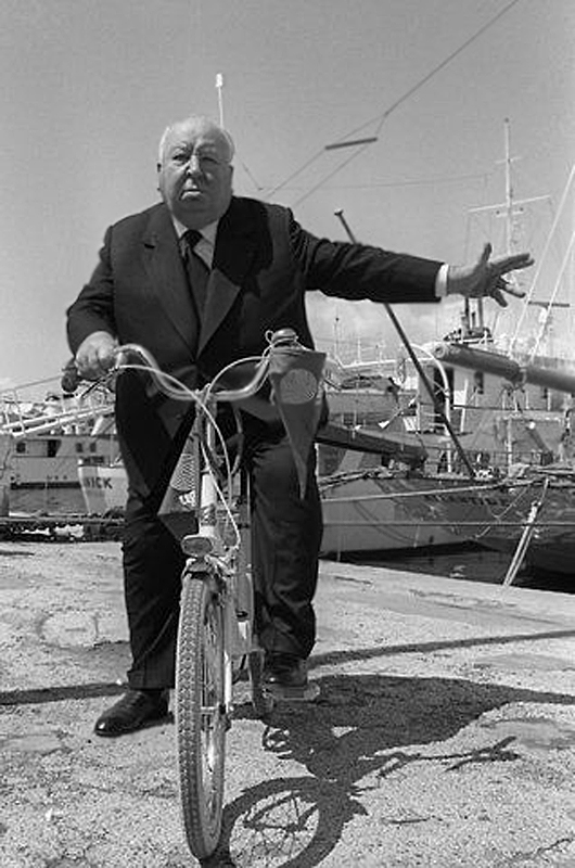 Alfred Hitchcock on a bicycle, apparently signaling a left turn