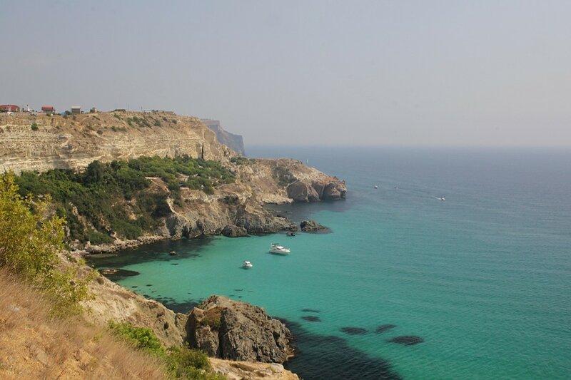 Скальные стенки и небольшая бухта с яхтами у мыса Фиолент (Севастополь, Крым)
