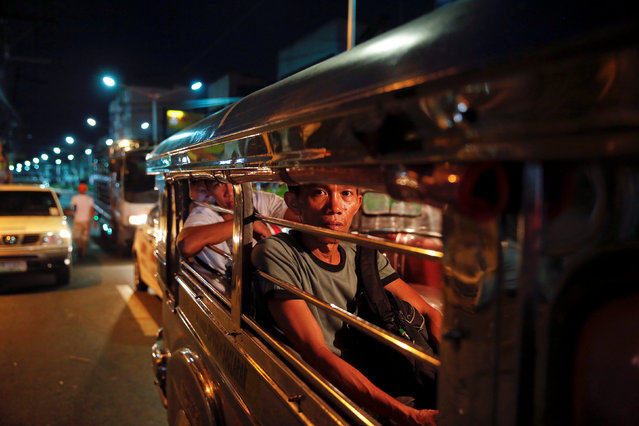 People look from inside a jeepney as police investigate around the body of a man killed by unknown g