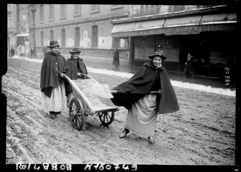 Women shovelling snow from the road Paris France