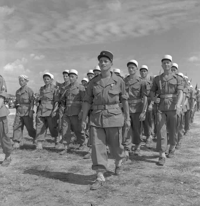 Du pas lent caractéristique de la Légion Etrangère, le 5e REI (Régiment Etranger d'Infanterie) défile au cours d'une prise d'armes à Ninh-Giang où ont été décorés par le général de Lattre de Tassigny ceux qui se sont distingués dans les combats de Nghia-L