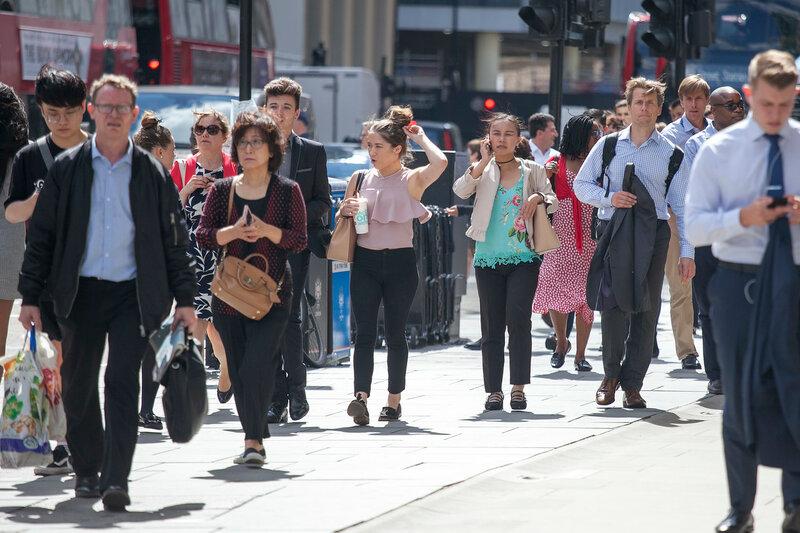 People across the road near Liverpool Street Station to trains and metro