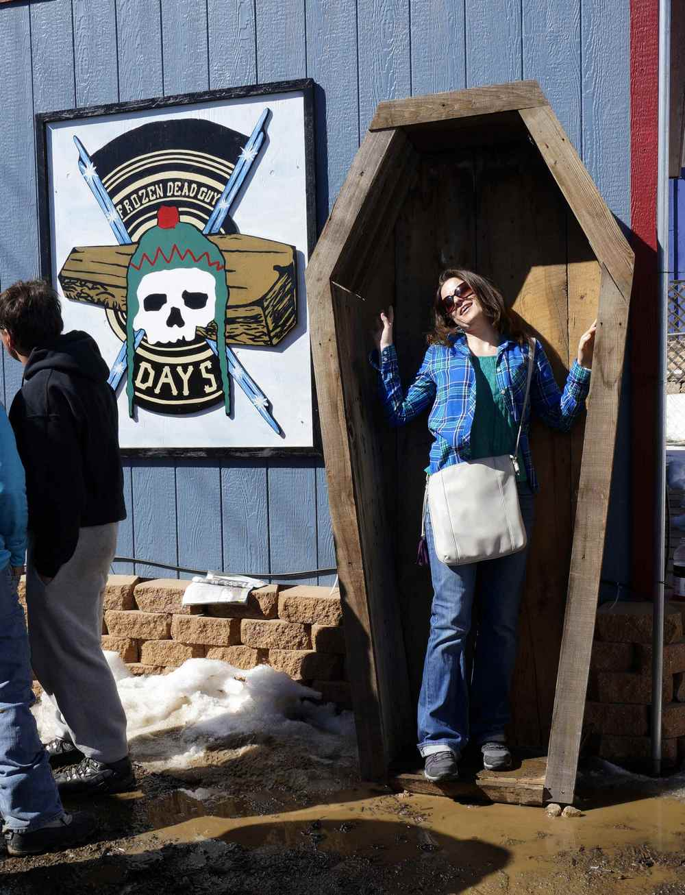 A woman poses for photo in coffin-shaped box at Frozen Dead Guy Days in Nederland