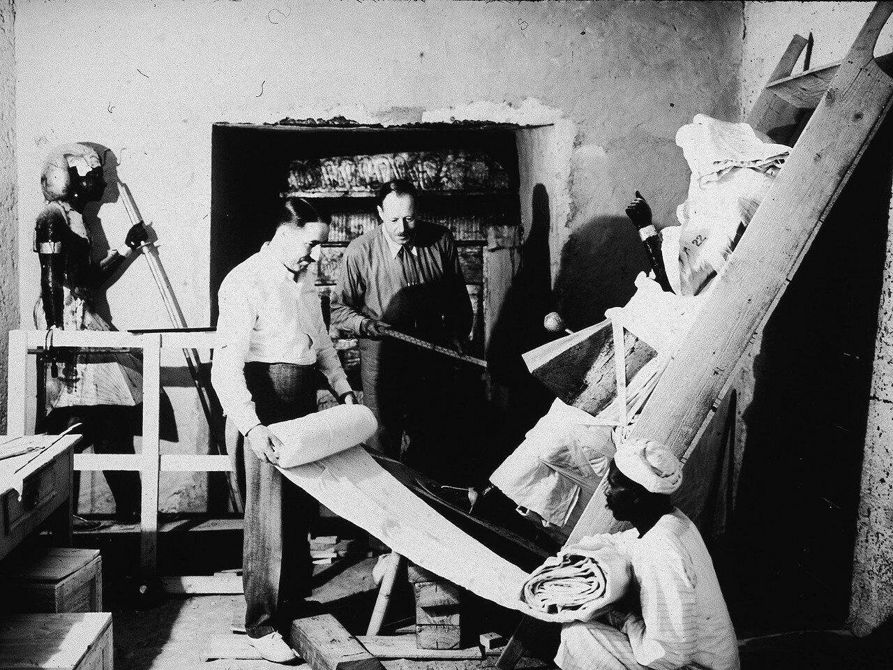 Британские археологи Говард Картер (слева) и Артур Каллендер извлекают предметы из гробницы фараона Тутанхамона с помощью египетского рабочего. 1923