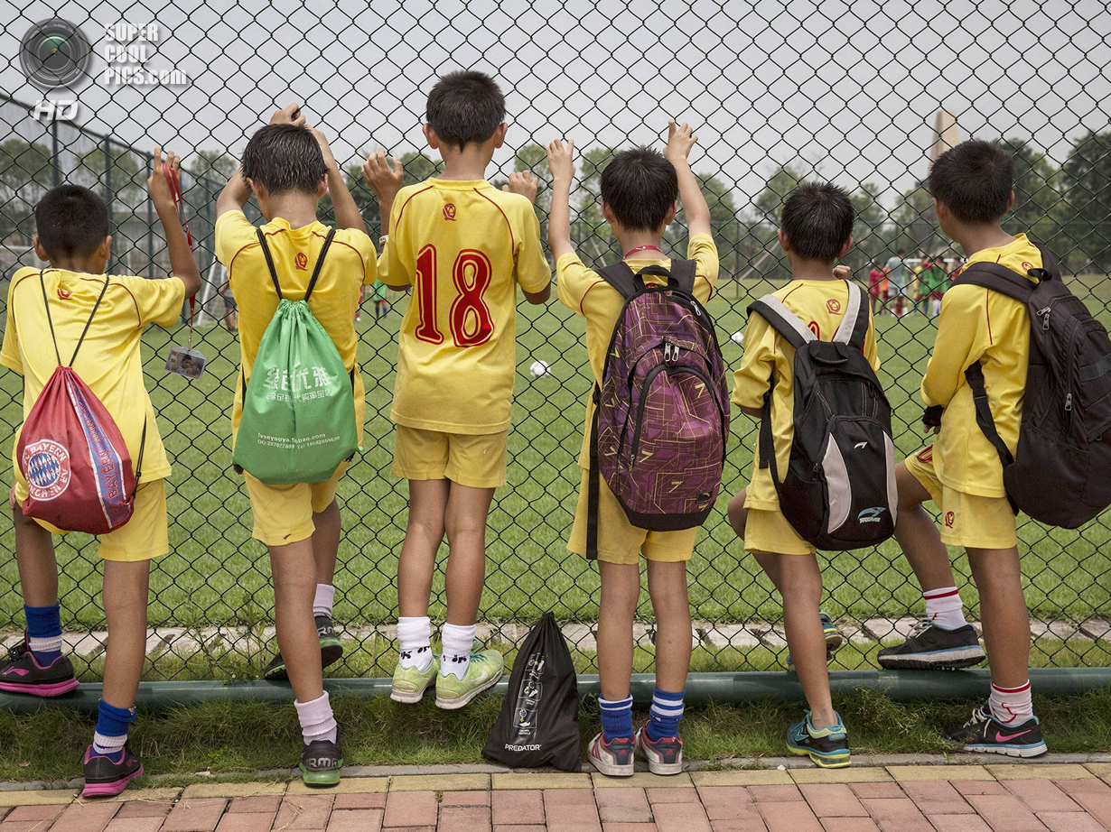Китай. Цинъюань, Гуандун. 13 июня. Мальчишки наблюдают за тренировкой своих товарищей. (Kevin Frayer