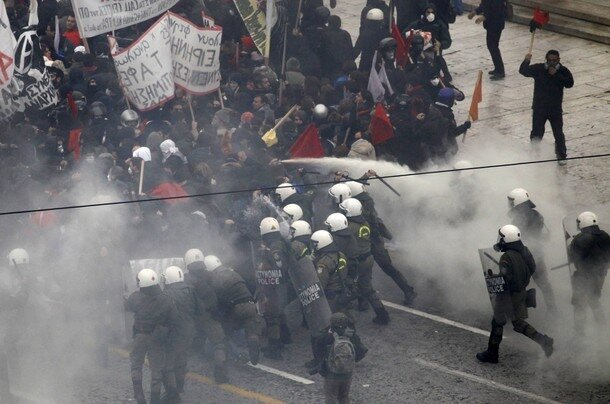 Police officers clash with protesters during riots in front of the parliament building in Athens