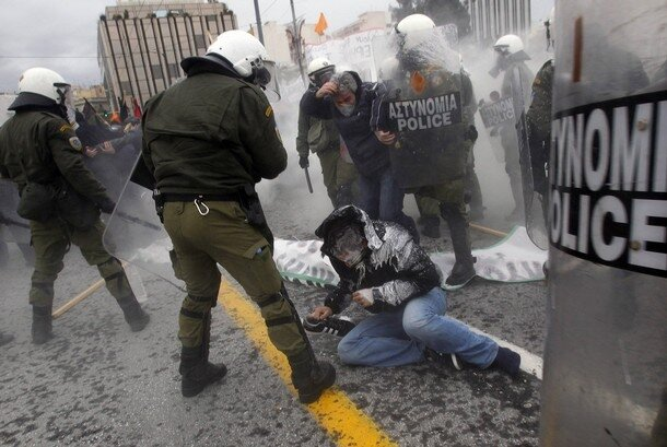 A protester falls on the ground during clashes in central Athens